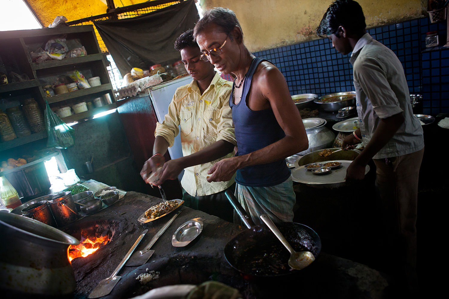 Three men working in a kitchen in a small restaurant in Bokaro- India