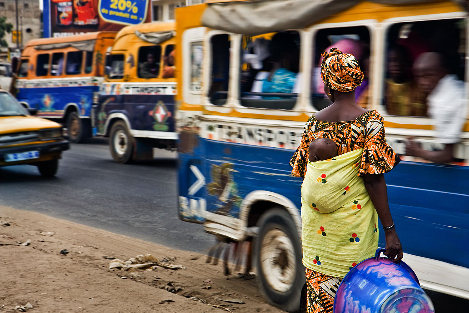 A woman with a child waits in the Dakar traffic. Senegal