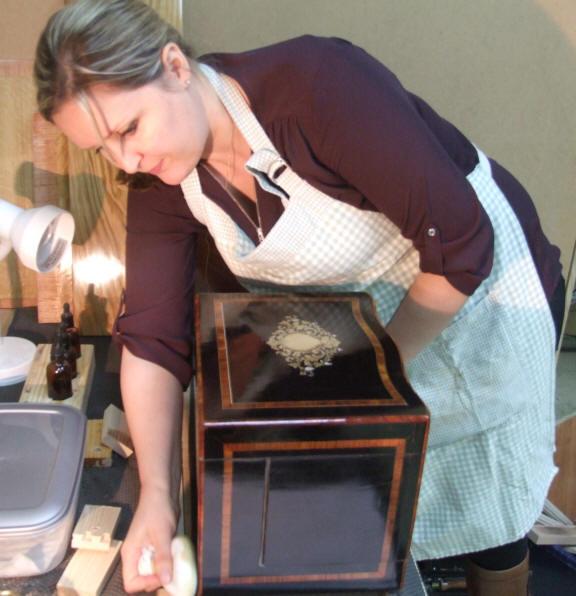A student polishing an ebony box