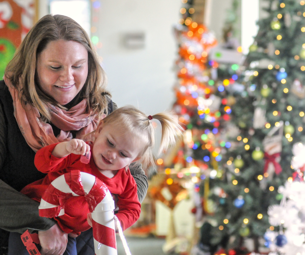 Marie Woodcock, left, holds her daughter Emma McKenna as she drops a ticket into a PVC pipe candy cane to vote for one of her favorite trees at the 2017 River of Trees event in downtown Augusta. Photo by Joe Phelan.