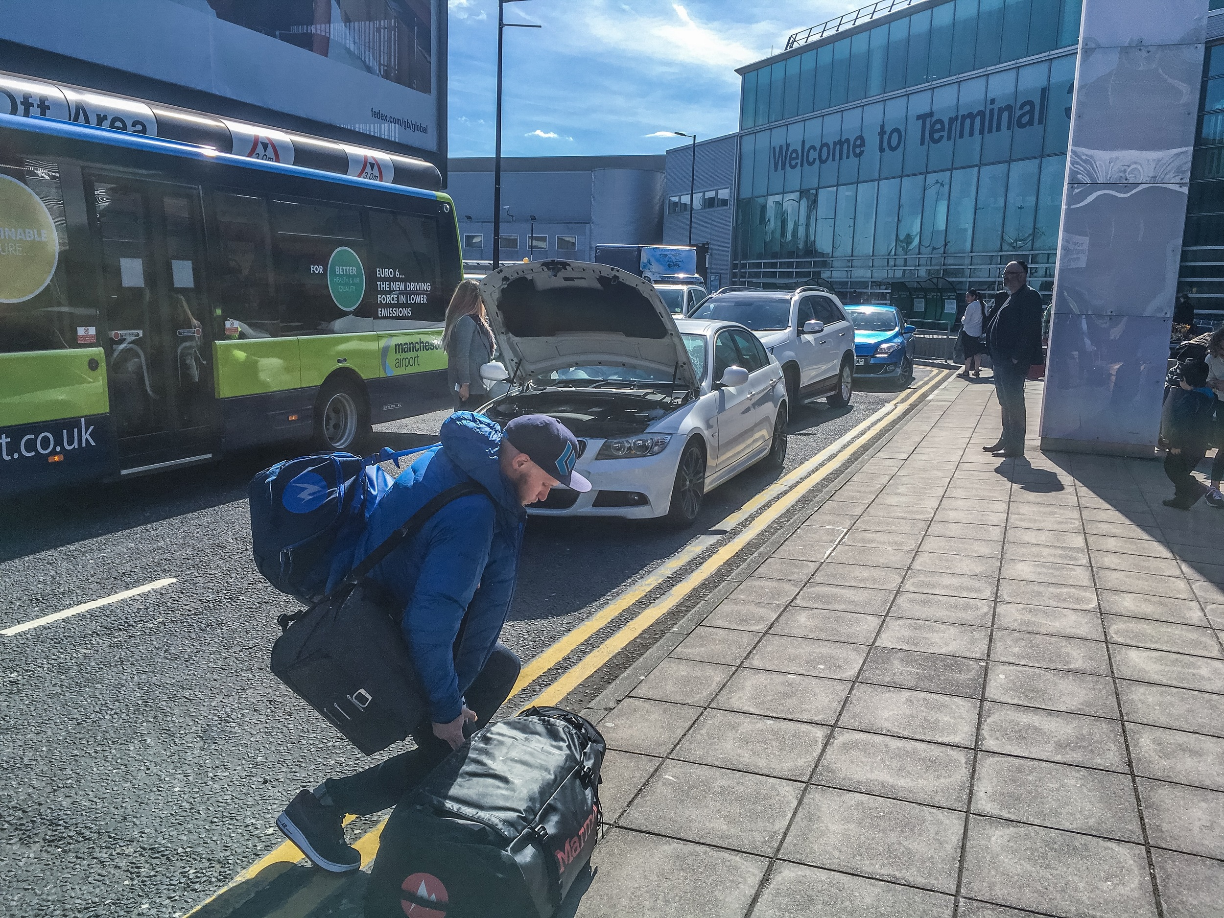 On tour. Manchester Airport for the ?th time this year.  In tow:x2 big duffles full of camera + climbing gear,x1 EDM that doesn't leave my side //  pic: L Lonsdale collection