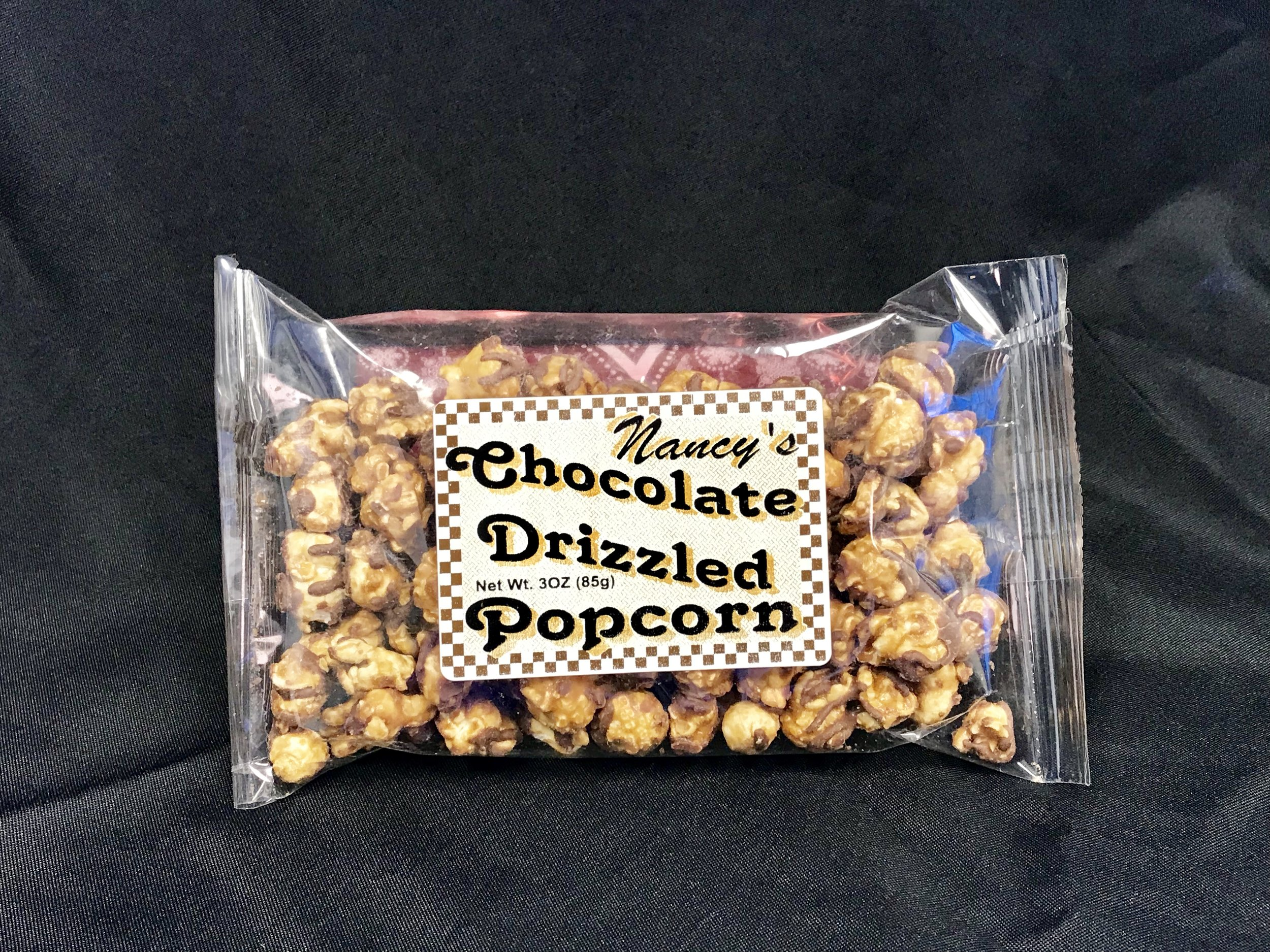 Milk Chocolate Drizzled Caramel Corn - 3 oz bag of delicious caramel popcorn drizzled with creamy milk chocolate. So delicious and makes the perfect holiday gift!