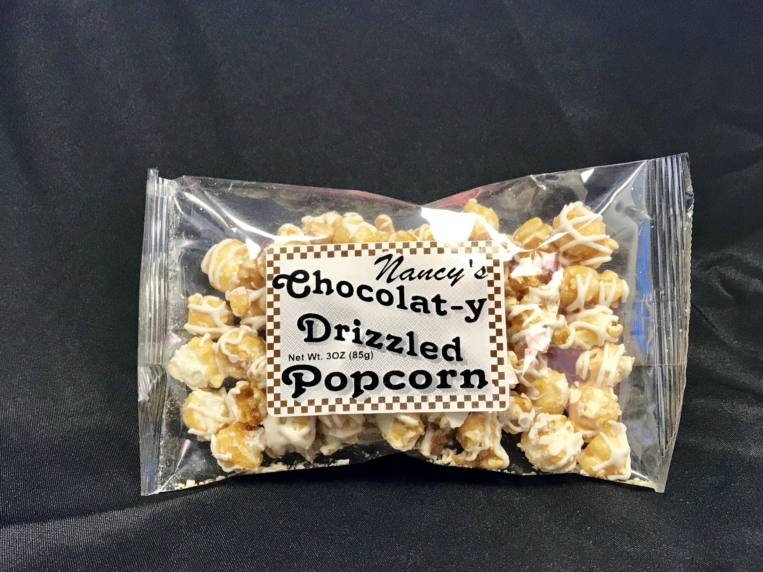 White Chocolate Drizzled Caramel Corn - 3 oz bag of delicious caramel popcorn drizzled with creamy white chocolate. So delicious and makes the perfect holiday gift!