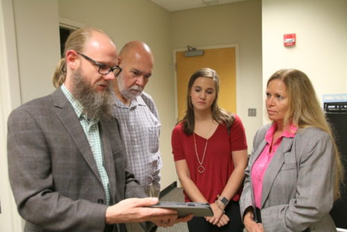 Walter Boot (left) demonstrates a computer system, specially designed for older adults at risk for social isolation, to staff members of Rep. Dunn's office (from left to right: staff members Will Kendrick, Meghan Myhill, and Amanda Daughtry).