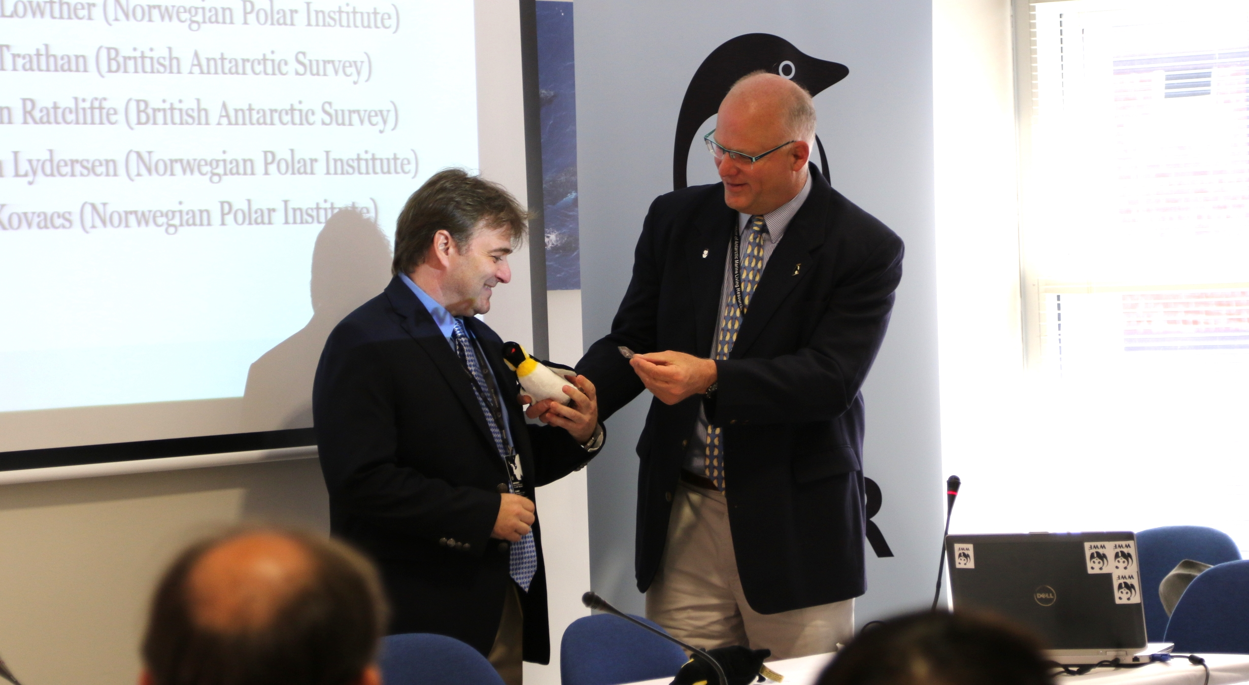 Werner handing over the AWR-penguin to Chris Reiss after his presentation on krill ageing methods. Photo: Monica Hägglund Langen