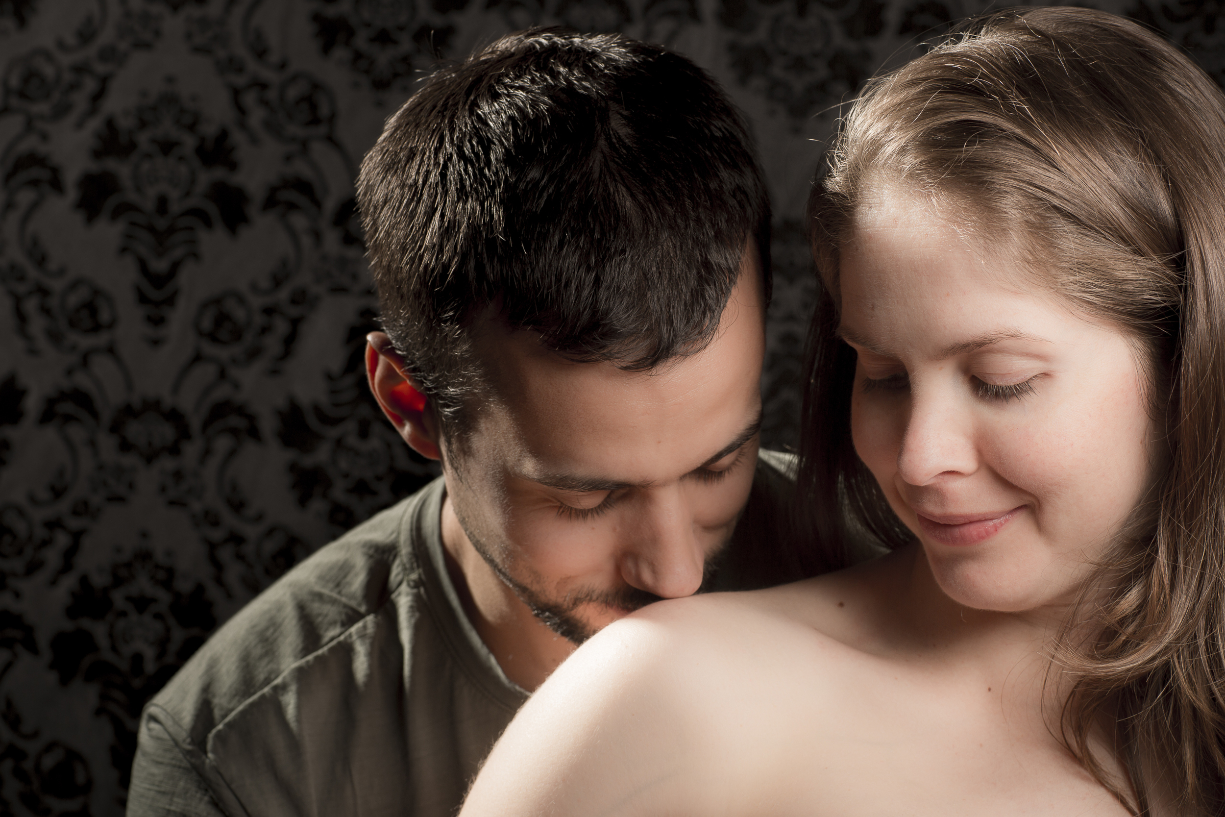 43 modern maternity photography studio session mom and dad kissing shoulder.jpg