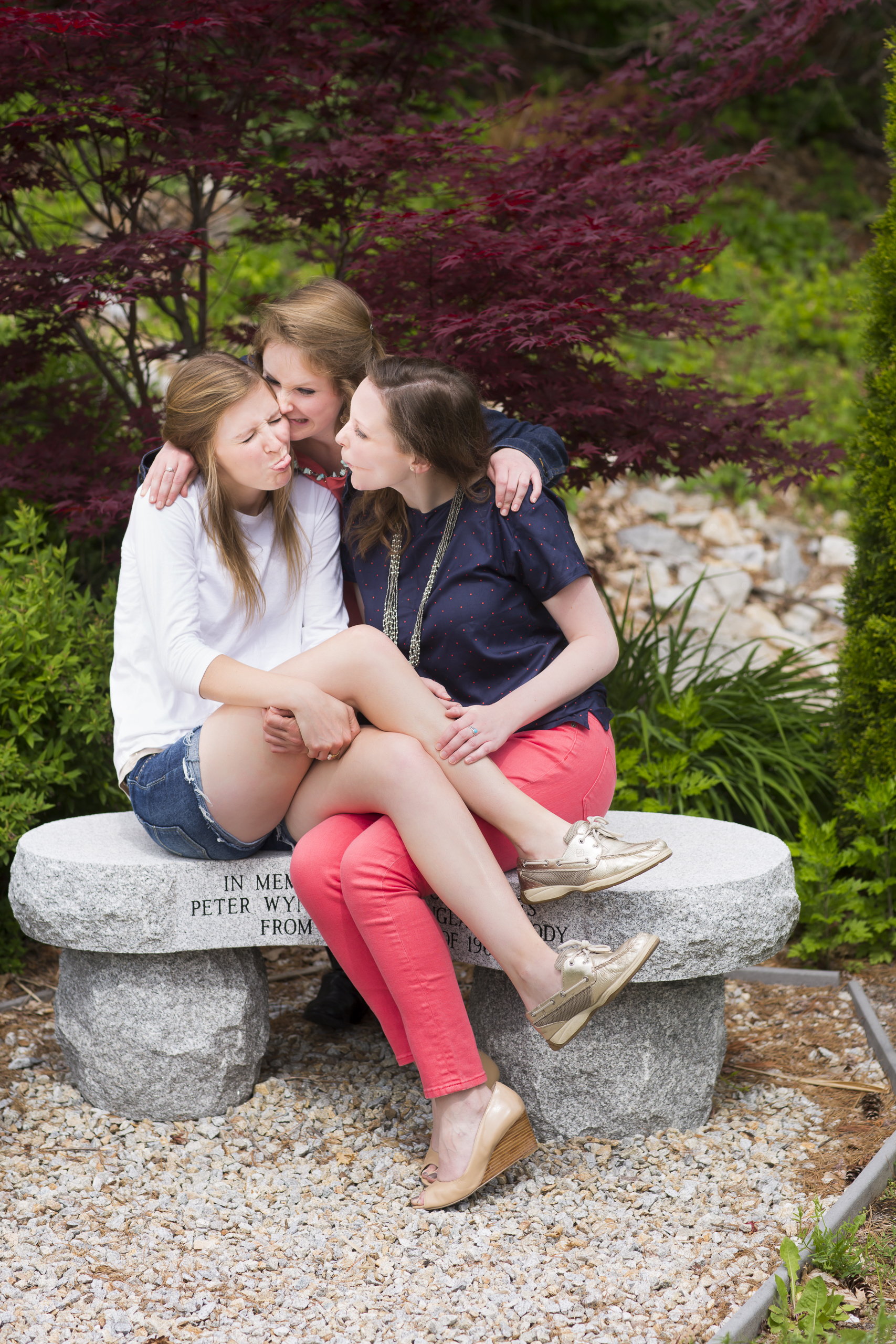 32 3 sisters family portrait outdoor session being silly on stone bench with red maple tree.jpg