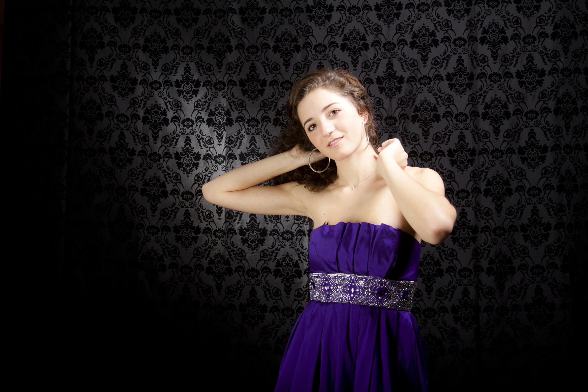 24 modern styled senior portrait session prom dress fixing hair on black background 9046.jpg
