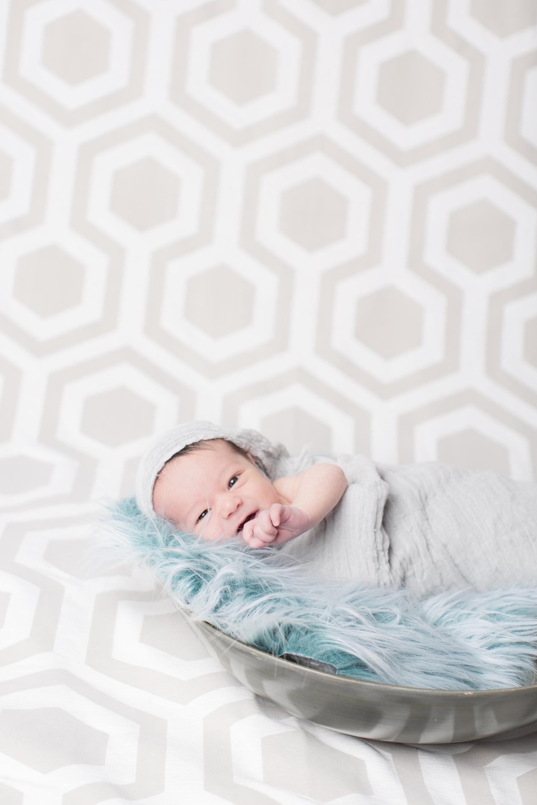 03 modern newborn baby boy blue swaddle in bowl modern hexagon backdrop studio photography session.jpg