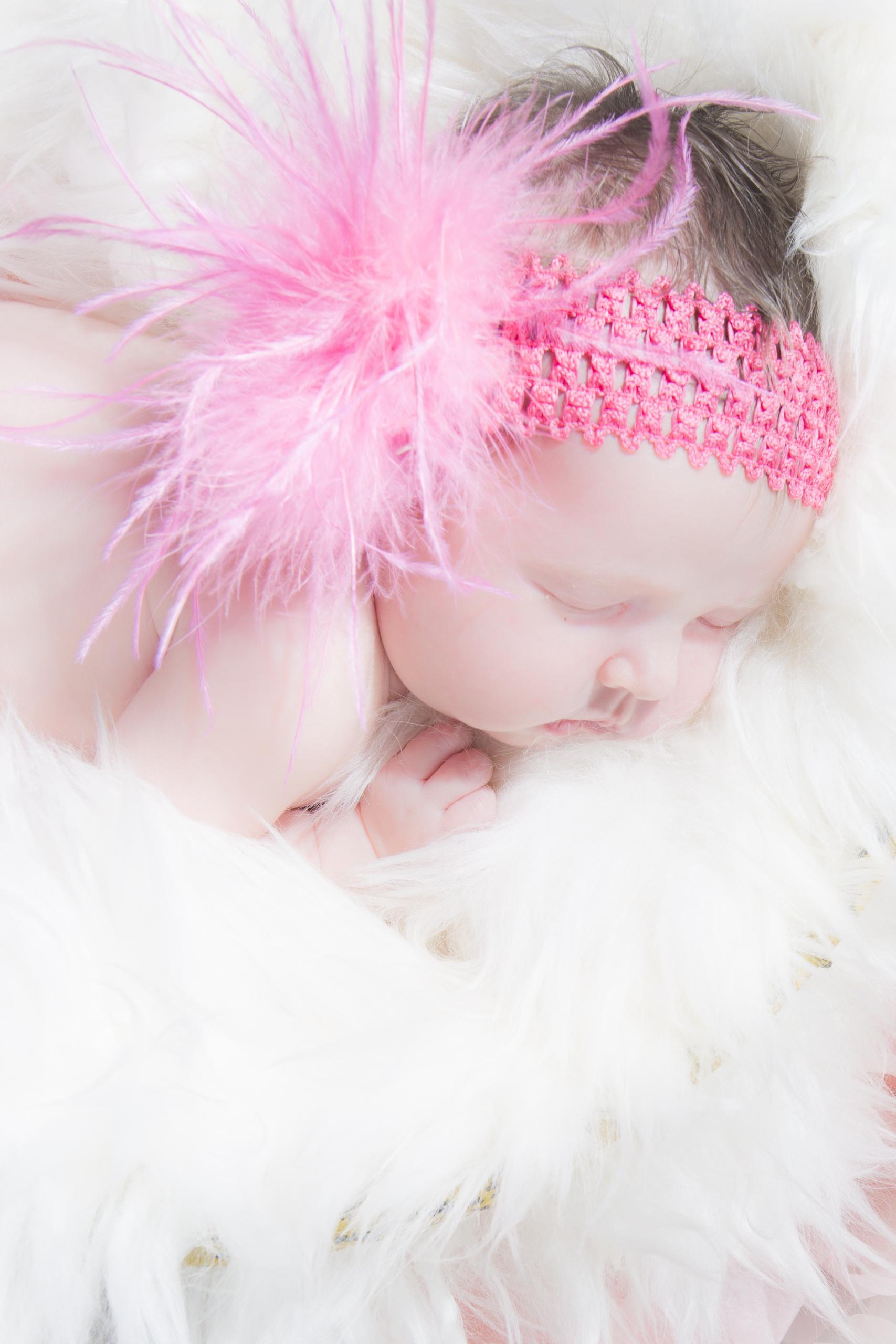 05 newborn girl pink feather headband fur rug basket studio photography session.jpg