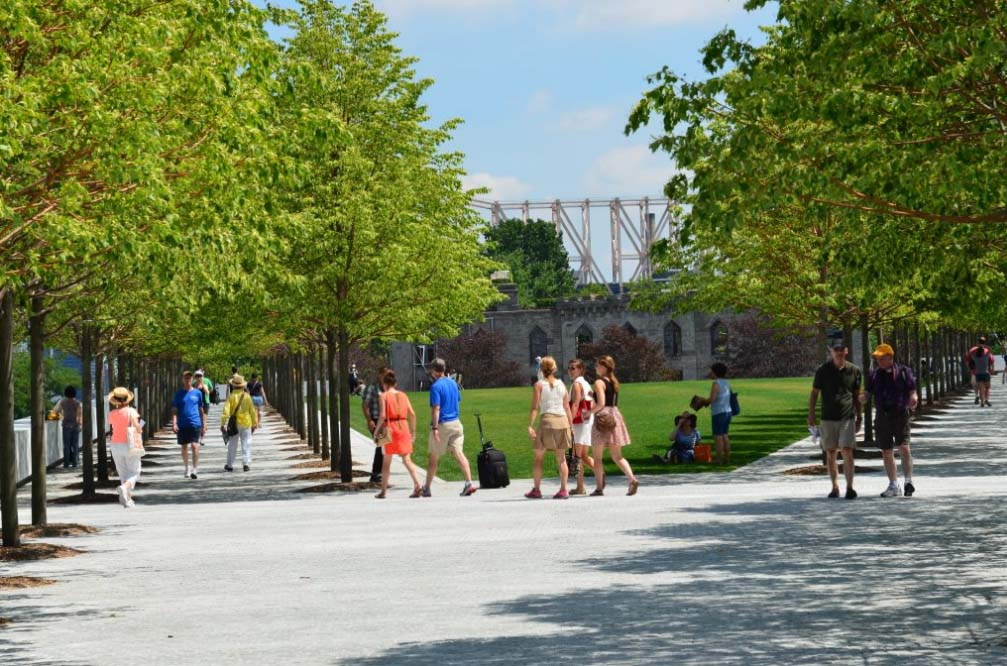 Park visitors on the lawn and strolling beneath the Littleleaf Linden trees.