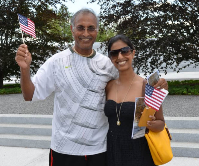 Park visitors near the Copper Beech trees, holding American flags.