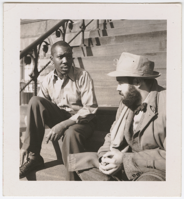 Artist Jacob Lawrence sitting on building steps with unidentified man, in Brooklyn, New York, 194