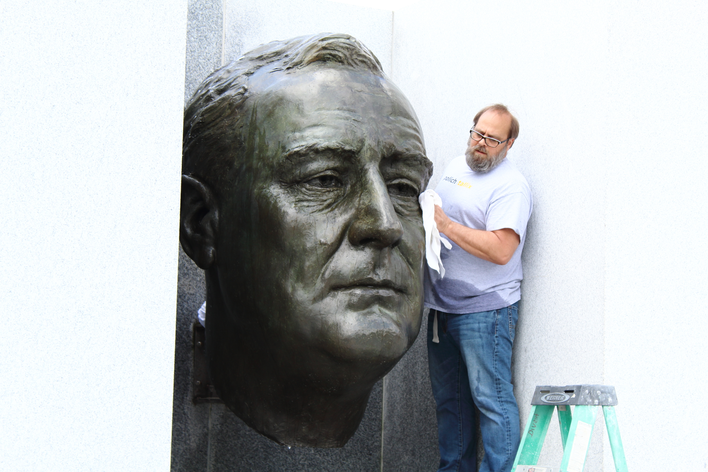 Pollich Tallix performances annual wax treatments on the bust. Photo by Michael Heck, Four Freedoms Park Conservancy.