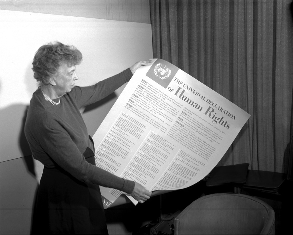 Eleanor Roosevelt holds a copy of the UDHR.