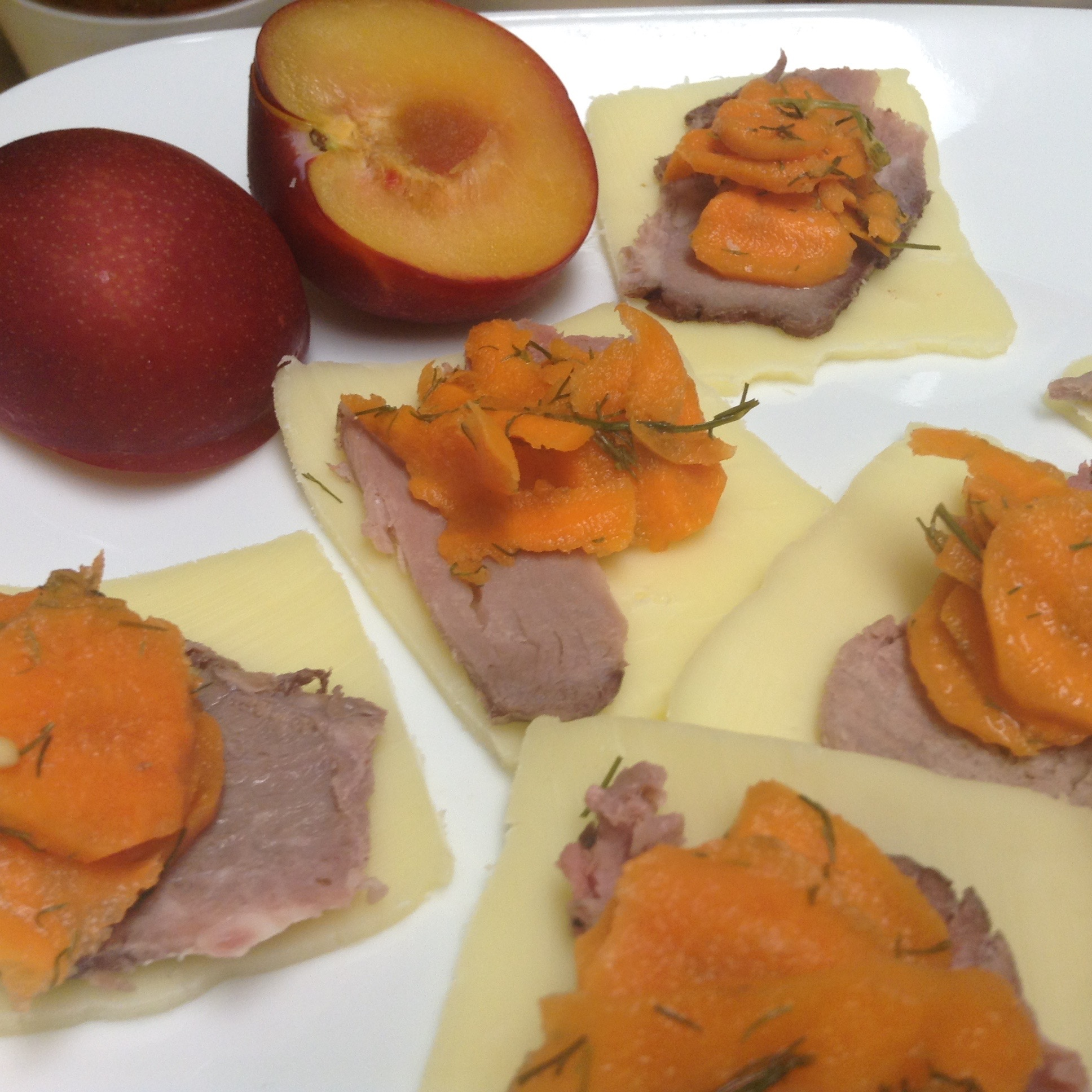 fermented dilly carrots on top of grass-fed beef slices and raw cheese