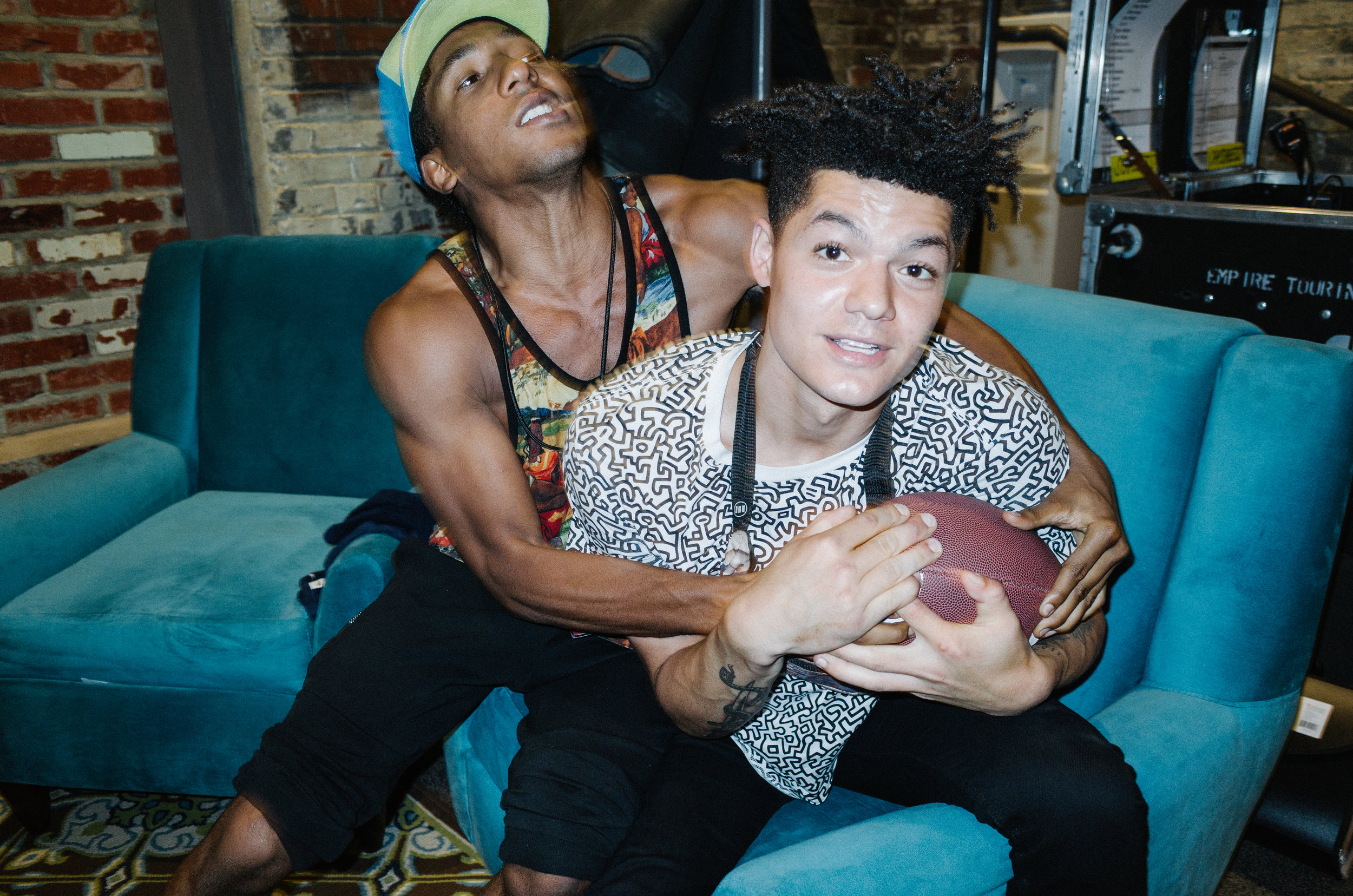 Damian and Alex fighting over a football backstage in Charlotte
