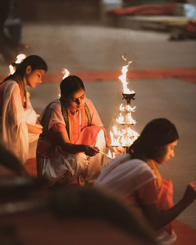 Young women light lamps during Ganga Aarti at dawn, a morning prayer meant to greet the river as the sun rises. They will then form a chorus to sing chants and prayers alongside young priests. More in today's story.