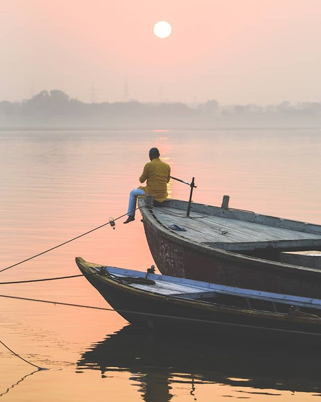 A man holds his hands in prayer as the sun rises over the #Ganges.