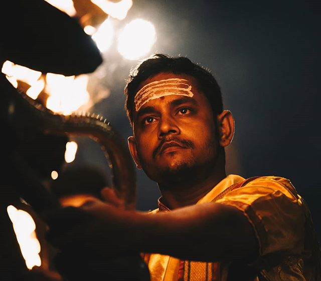 A close up of a priest as #Aarti is performed. During, large lamps are rotated in coordination while facing the river. It is believed that this bestows the blessings of the river to the lamps, which devotees are then able to collect by cupping hands over the flames after the ceremony.