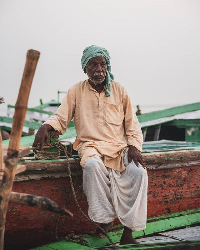 After dropping off passengers for morning prayers, a raftsman waits by his boat.