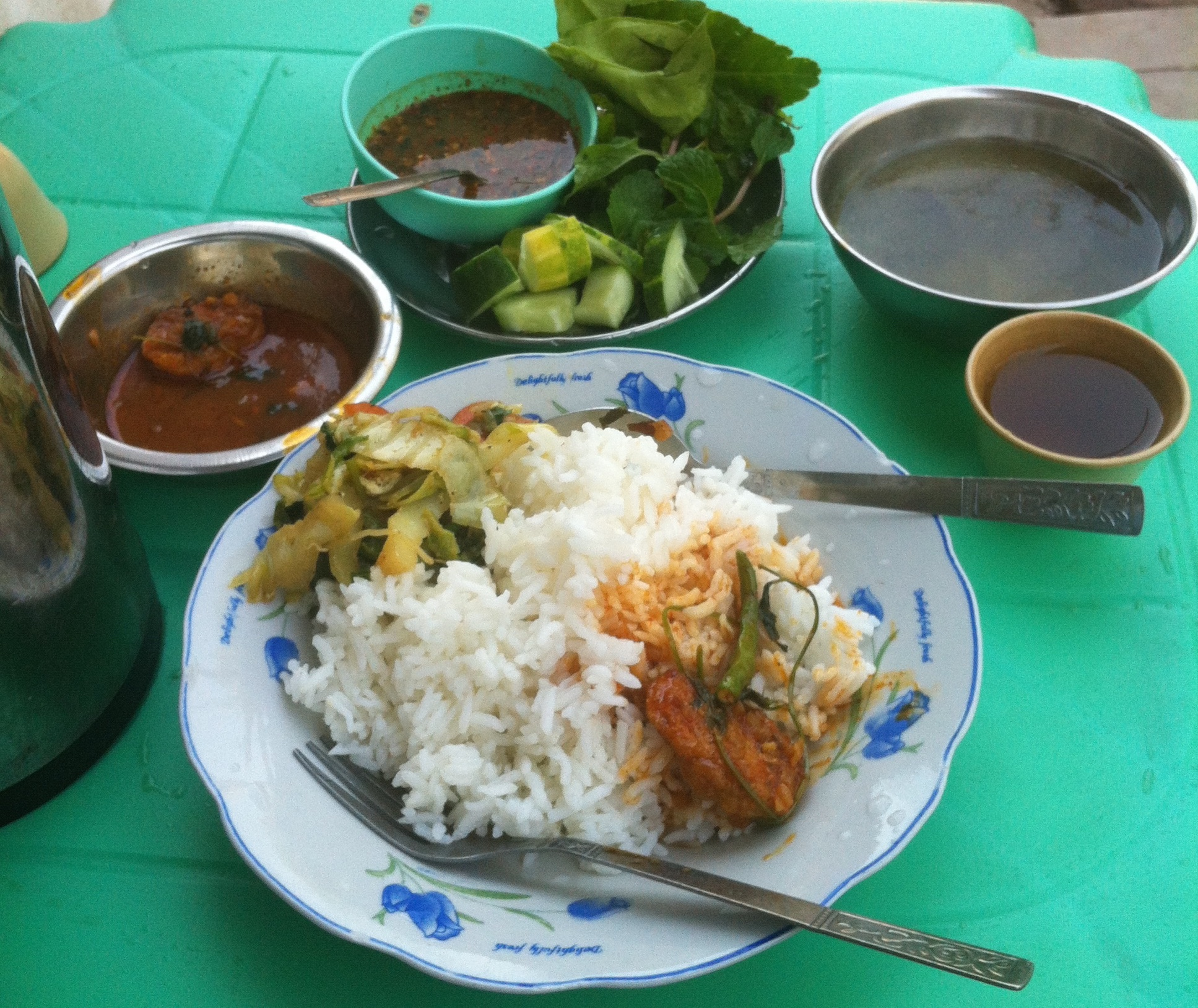 Curried fish filets and all the trimmings: cabbage, vegetable tray with spicy fish-sauce dip, sour greens soup, and tea. $1