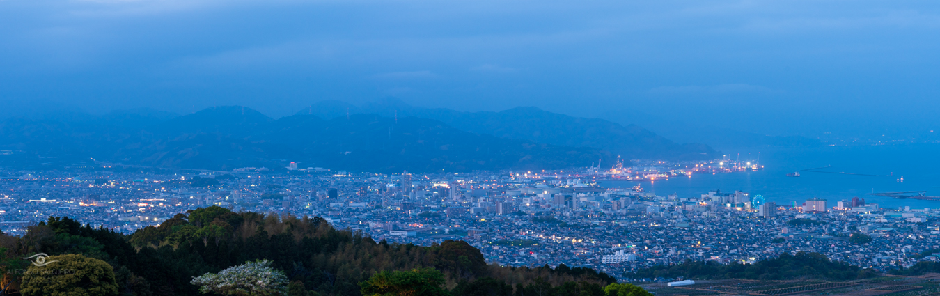 The hills of Shizouka with the city below and the hidden Mt. Fuji beyond during blue hour.