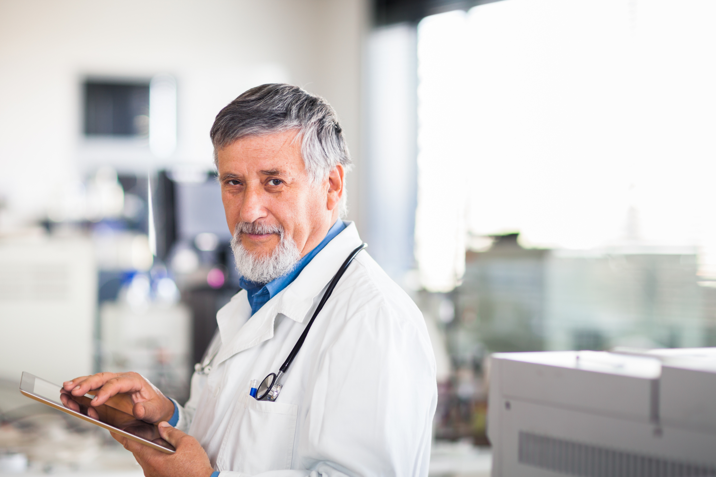 stock-photo-senior-doctor-using-his-tablet-computer-at-work-color-toned-image-99130298.jpg