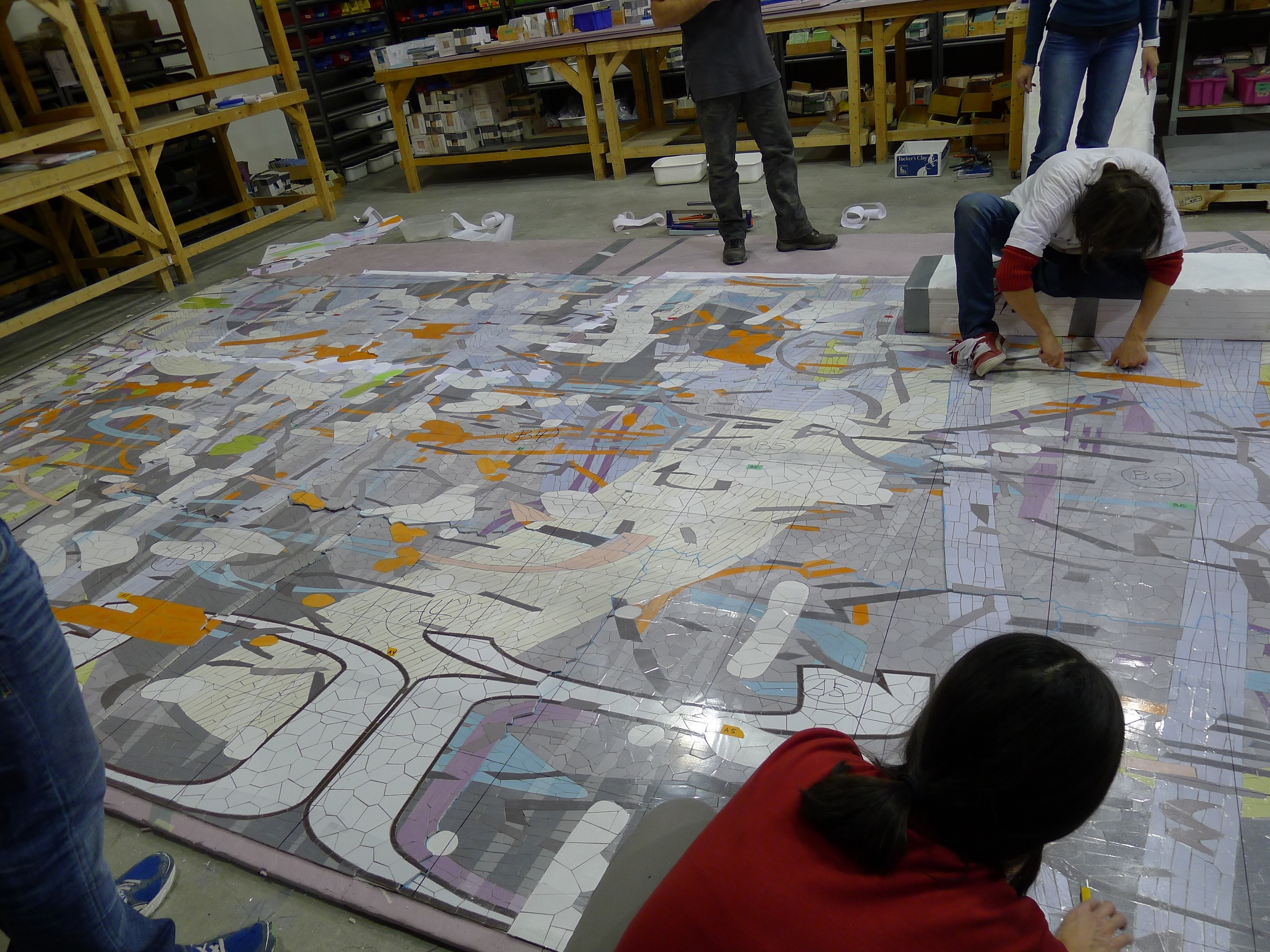 Artists sealthe mosaic between two sheets ofclear plastic and draw a grid onto the surface. It is then cut into smaller sections for crating and shipping.