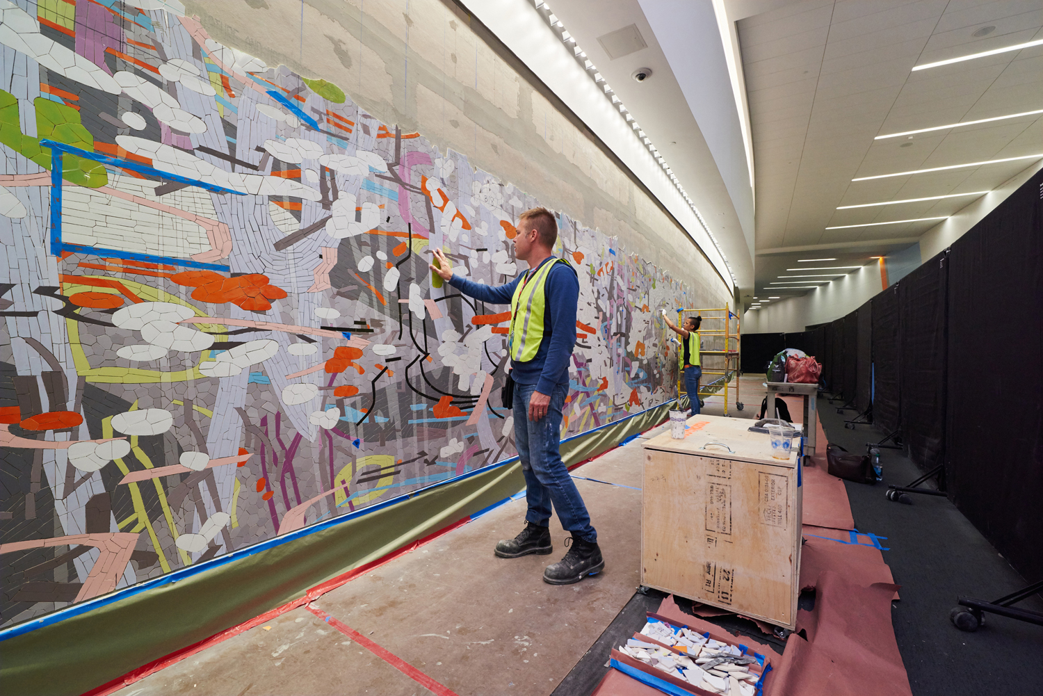 Mike checks the surface of the mural. The blue rectangle indicates a grout test area.