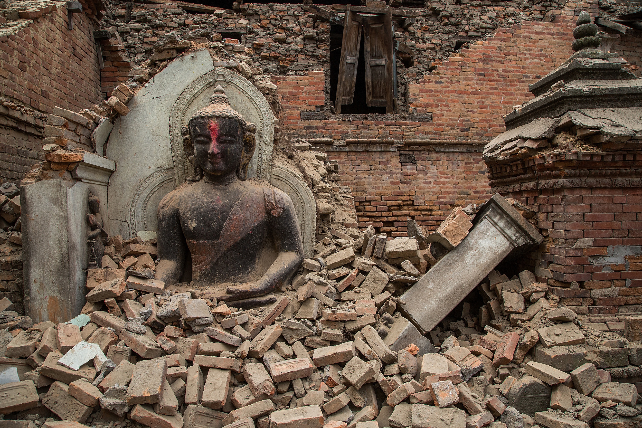 A Buddha statue is surrounded by debris from a collapsed temple in the UNESCO world heritage site of Bhaktapur on April 26 in Bhaktapur, Nepal.     (Photo: Omar Havana, Getty Images)