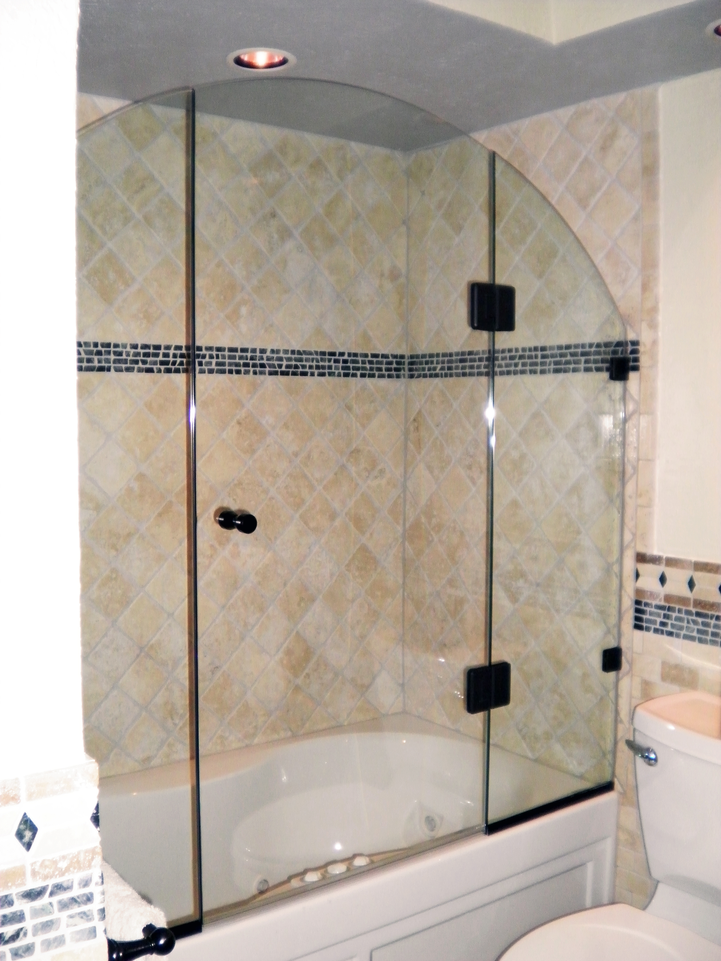 #8. This 3-piece inlineframeless solution features channel supports where the glass meetsthe tub. Glass-to-glass hinges allow the door to be in the center for optimal function and access.Beveled black hinges resonate with black tile accents and round out the look.