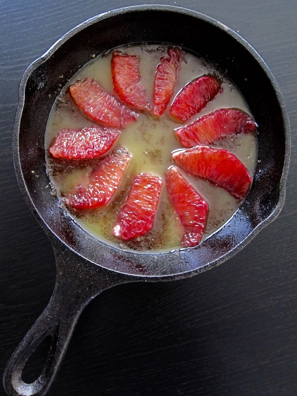 blood orange sections arranged in skillet