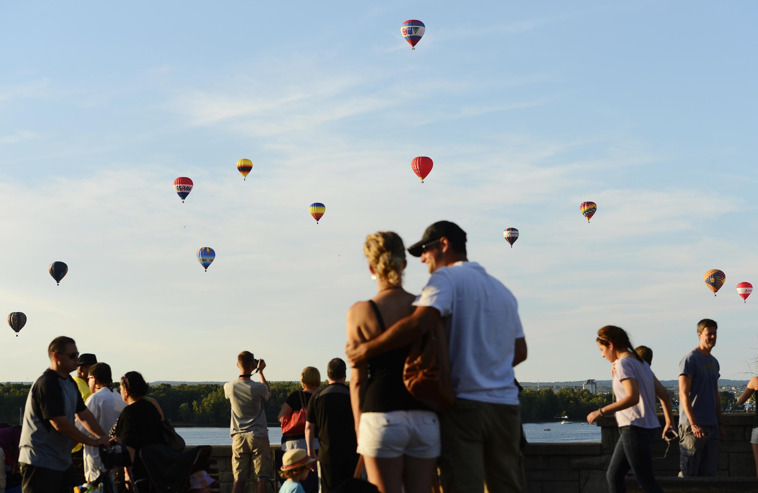 Hot air balloons rise over Ottawa river from Gatineau Hot Air Balloon Festival.