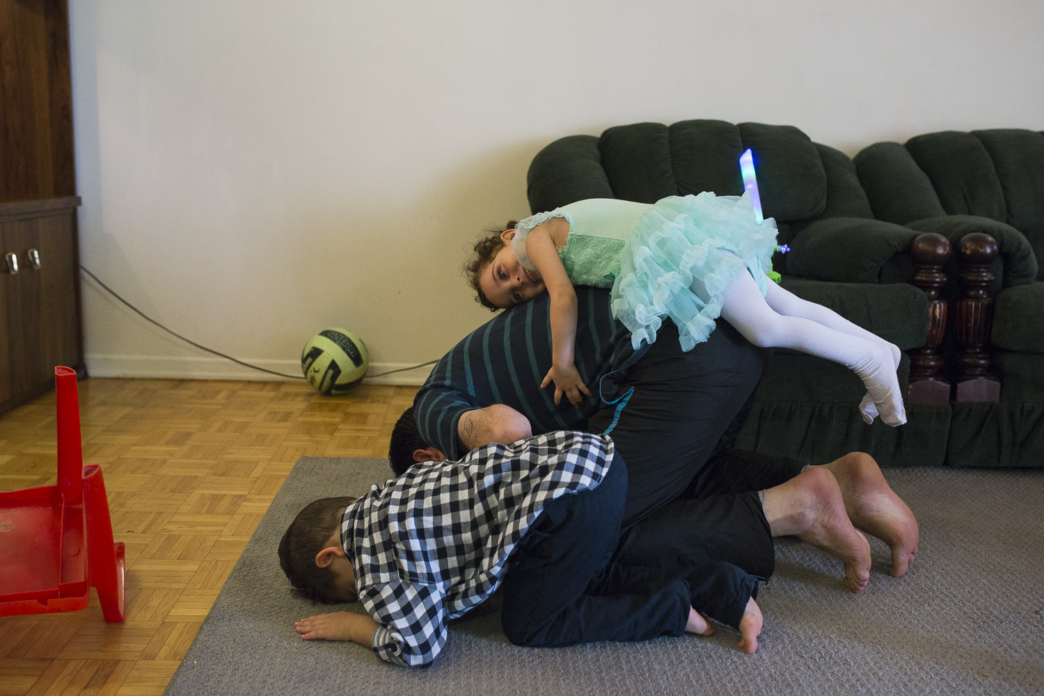 His daughter hugs him from the back during his prayer at home.