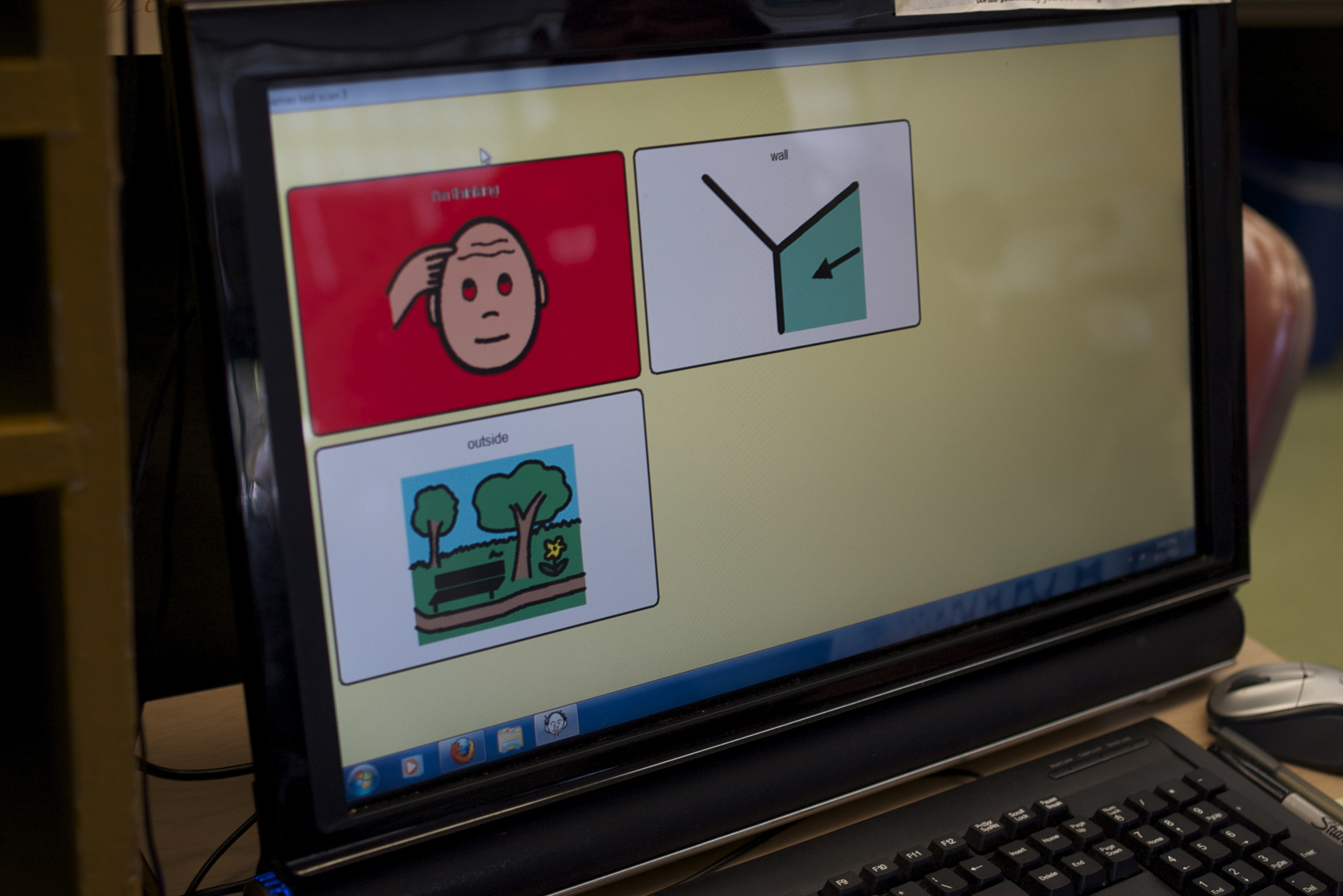 Several nonverbal students use Augmentative and Alternative Communication systems that consist of a speaker board pre-populated with images and words. Teachers and caregivers update the vocabulary based on the student's needs.
