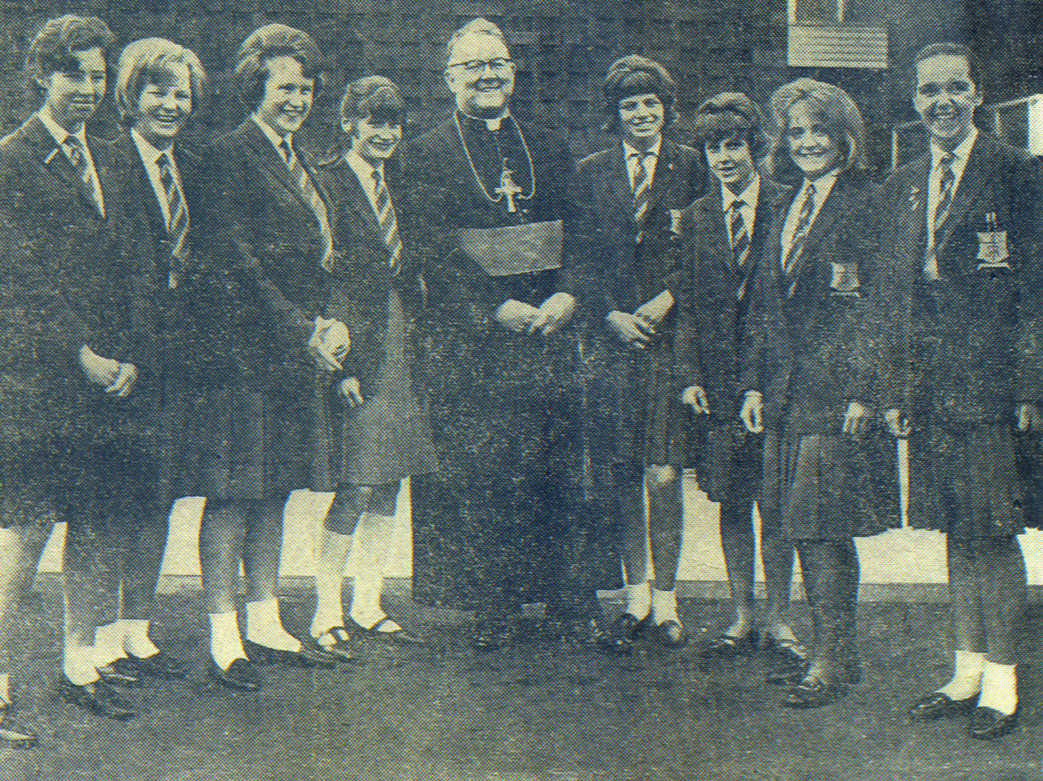 Photo: Bishop Dwyer talks with St. Mary's pupils after performing the official opening, 3 July 1965  LEFT TO RIGHT: Josephine Joyce, Ruth Copsey, Brenda Hope, Marilyn Dix, Anne Mahon, Stella Kent, Kathleen Lawson and Rosaleen Doran  Photograph kindly donated by Rosaleen Doran (Fisher) Head Girl