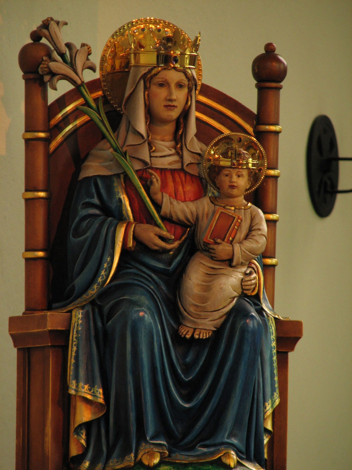 Photo:Our Lady, as she is venerated at Walsingham, is depicted as a simple woman, a mother. She is seated on the throne of Wisdom, in the midst of the Church which is represented by the two pillars symbolic of the Gate of Heaven, with seven rings to signify the seven sacraments and the seven gifts of the Holy Spirit.