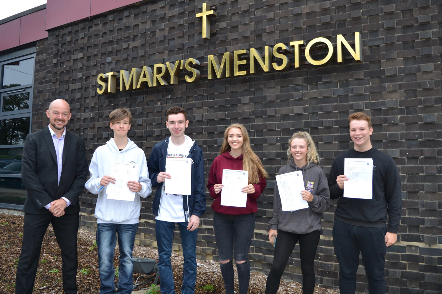 PHOTO: Mr Harvey (Student Progress Leader, Year 11 2015–16 and Year 11 pupils with their results, 25 August 2016