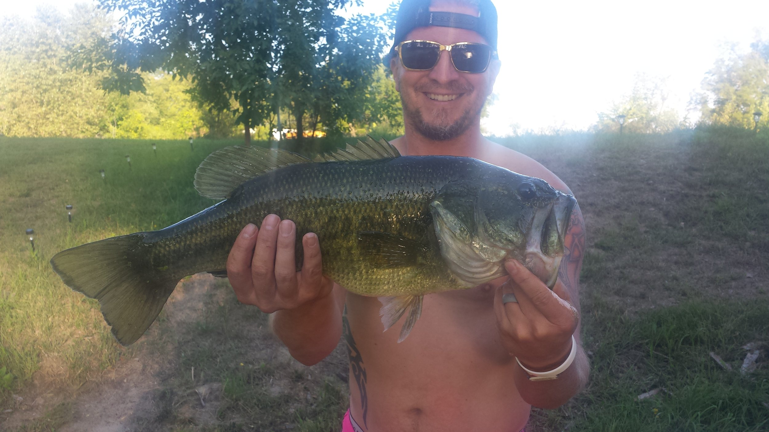 Brett hooking a big one out of our pond that has an impressive combination of both length and girth.