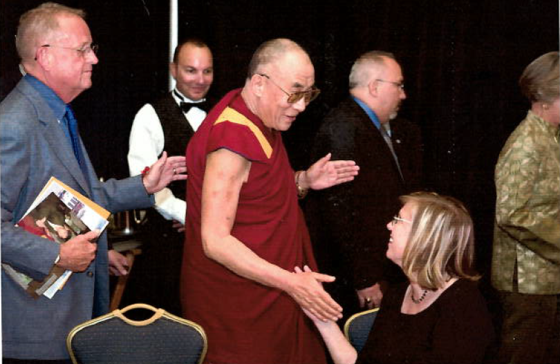 The Dalai Lama gives a low five to Steve's partner, poet and teacher Dana Teen Lomax.
