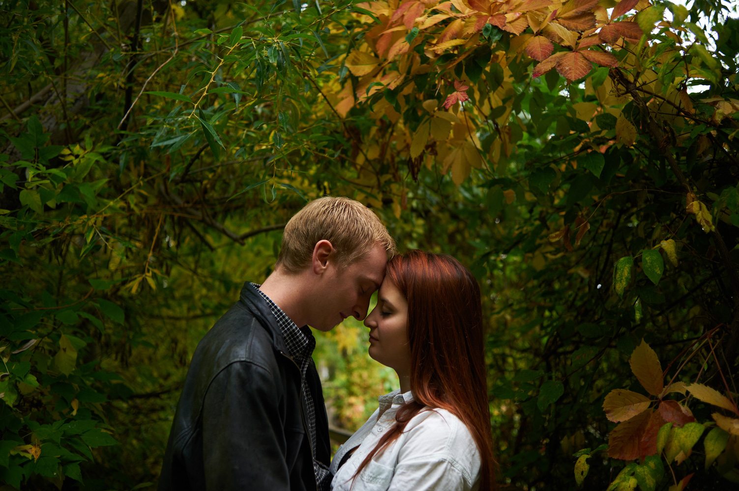 engaged-couple-amongst-colored-leaves-in-fall.jpg