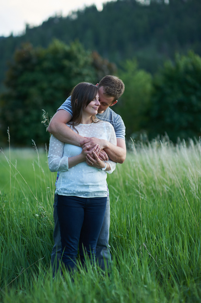 engaged-couple-embracing-in-a-grassy-field-at-sunset.jpg