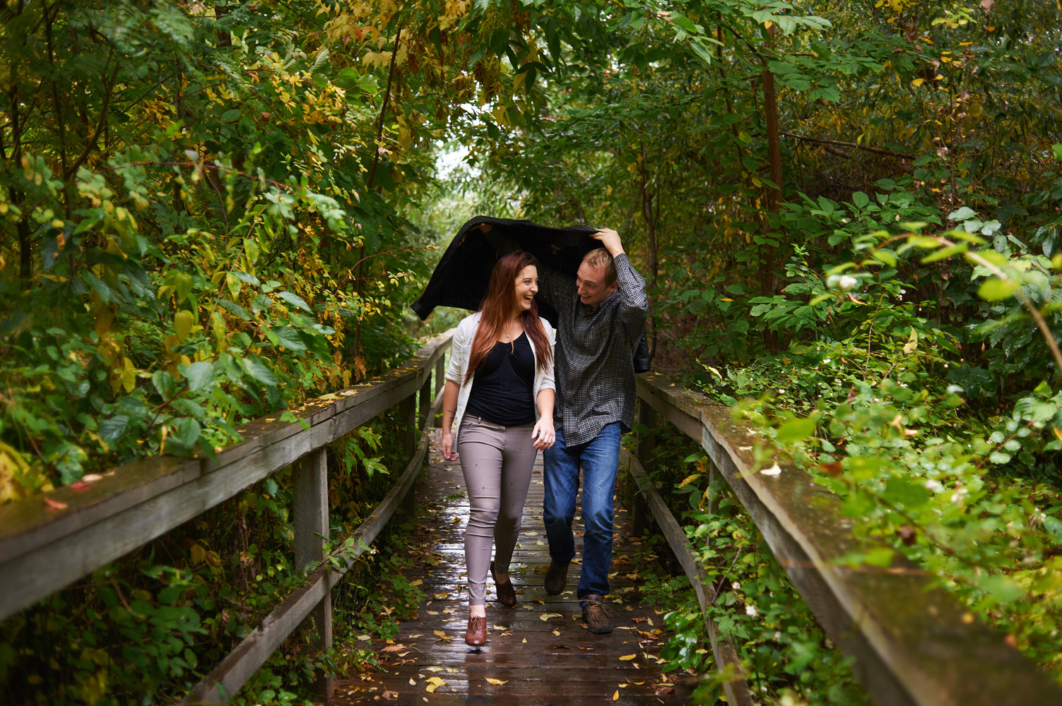 engaged-couple-running-in-the-rain-down-a-boardwalk.jpg