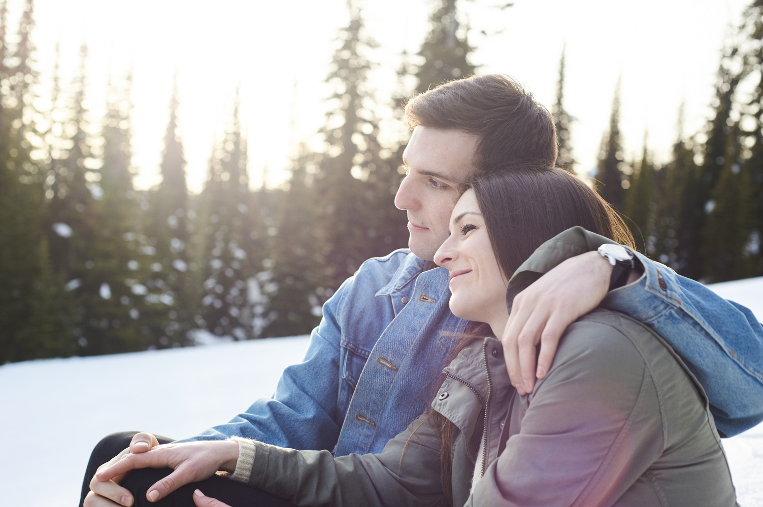 engaged-couple-snuggling-in-the-snow-at-big-white-sunset.jpg