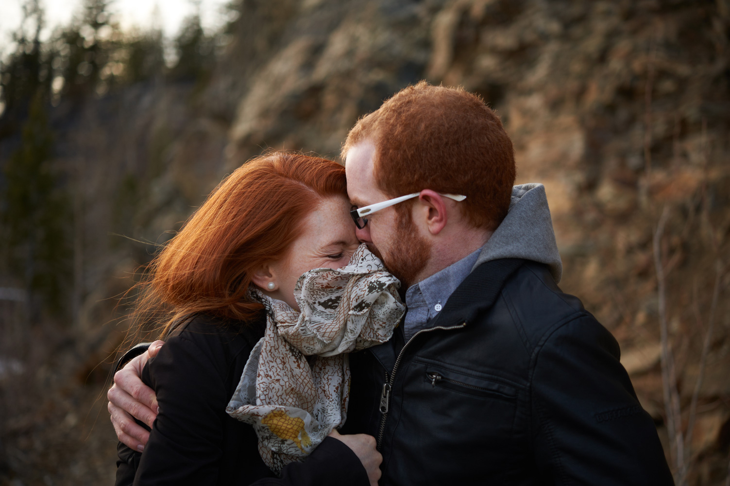 engaged-couple-snuggling-in-the-breeze-in-front-of-rock-face.jpg