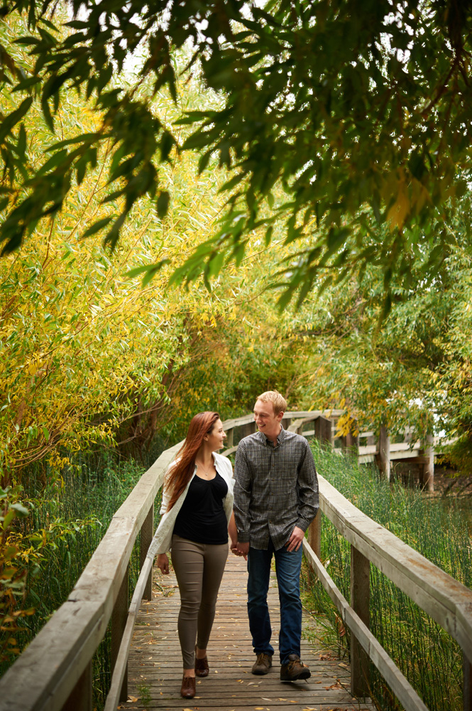 engaged-couple-walking-hand-in-hand-down-a-boardwalk-in-fall.jpg