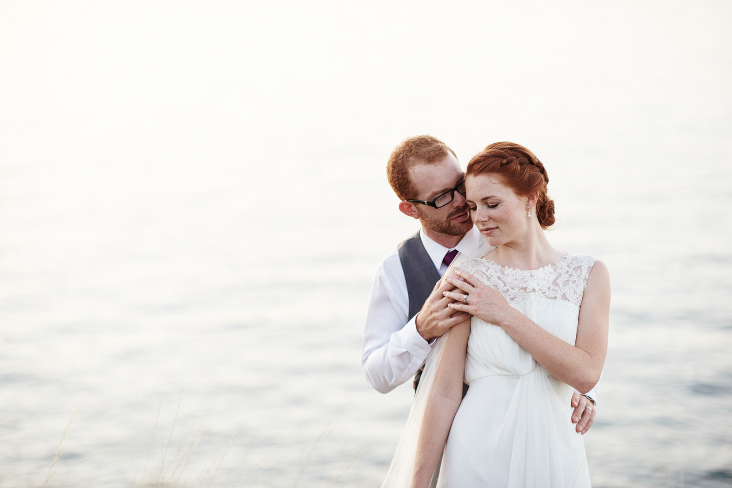 bride-and-groom-standing-by-the-lakes-edge-in-the-twilight.jpg