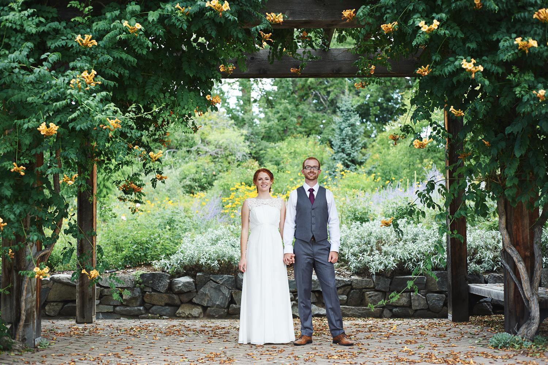 bride-and-groom-standing-hand-in-hand-under-a-wooden-trellis.jpg