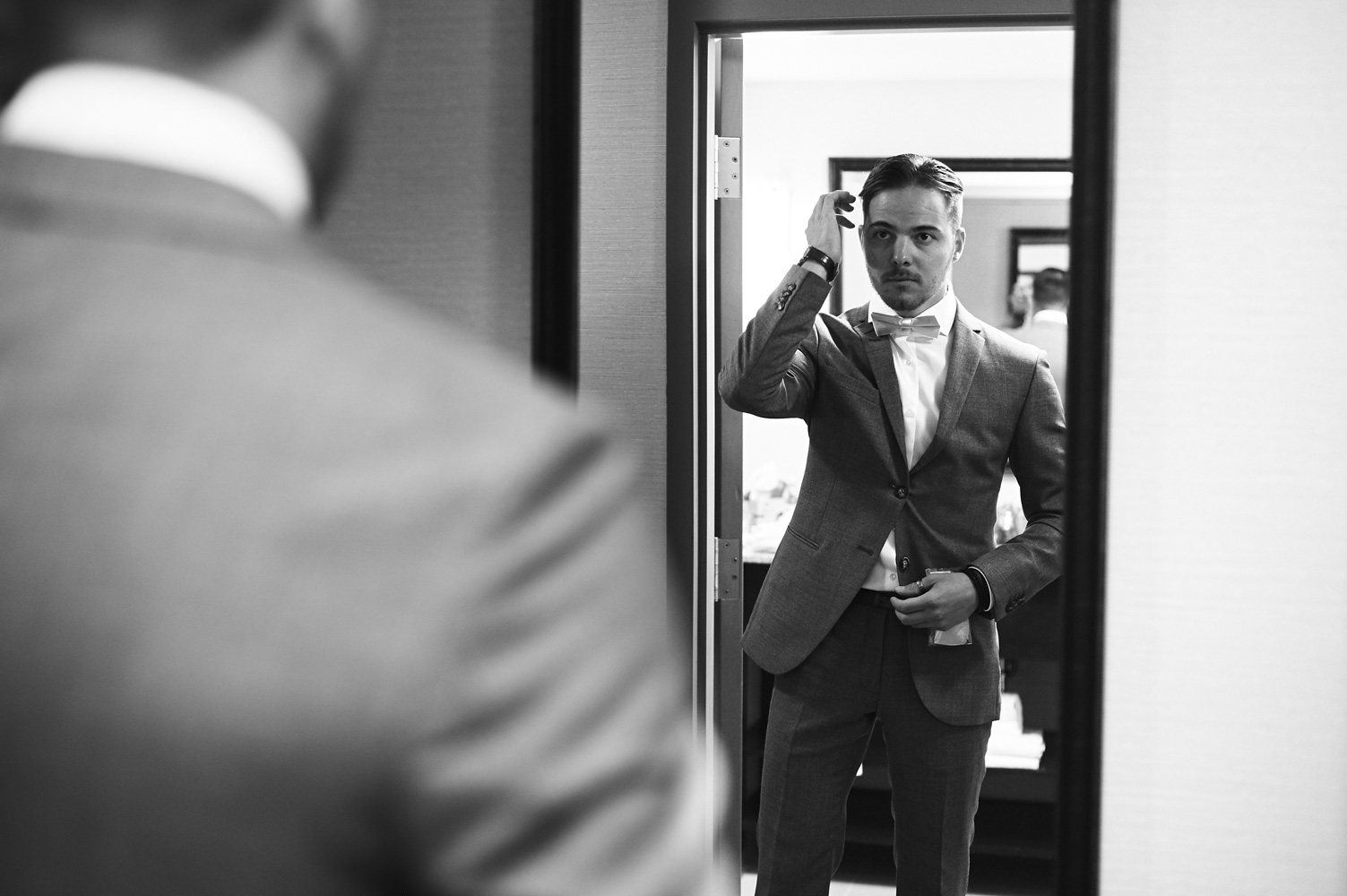 black-and-white-portrait-of-the-groom-looking-at-his-reflection.jpg
